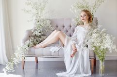 Girl white light dress and curly hair, portrait of woman with flowers at home near the window, purity and innocence. Curly blonde stock photography