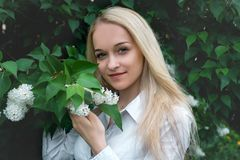 Girl with white lilac and green foliage , portrait of a girl stock photography