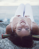 Girl in white is lying on the beach and smiling, sunset royalty free stock image