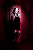 Girl with white mask on red background Stock Photography