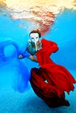 The girl in the white mask swims underwater with red and blue fabrics on the background of the sunset and looking at the camera. Portrait. Vertical orientation Stock Images