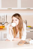 Girl a white men's shirt with long flowing hair is drinking tea  kitchen elbows on table. morning Stock Images