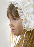 Girl in white old fashioned lace cap. Portrait of a beautiful little girl, side view and black background Stock Photo