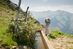 Girl in white pants and a blue blouse washes at a mountain spring royalty free stock photo