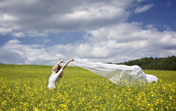Girl with white piece of cloth in wind. Young happy woman standing in yellow rapeseed field holding a white long piece of cloth in the wind expressing freedom Royalty Free Stock Photography