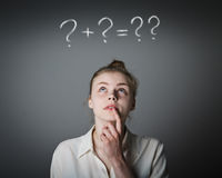 Girl in white and question marks. Girl in white full of doubts and hesitation. Girl and question marks above her head. Young slim woman royalty free stock images
