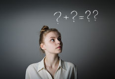 Girl in white and question marks. Girl in white full of doubts and hesitation. Girl and question marks above her head. Young slim woman stock image