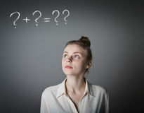Girl in white and question marks. Girl in white full of doubts and hesitation. Girl and question marks above her head. Young slim woman stock photography
