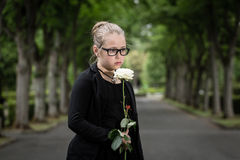 Girl with white rose mourning deceased on graveyard Royalty Free Stock Image