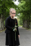 Girl with white rose mourning deceased on graveyard Stock Photos