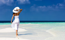 Girl in white on a sandbank in the Maldives Stock Images