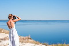 A girl in a white sarafan stands and takes pictures of the beautiful nature of rocks and water. Cliff, ridge, canyon. Refuge, rest stock photo