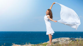 Girl with White Scarf on the Rock. Freedom Concept. Girl with White Scarf standing on the Rock stock photography