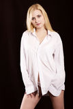 The girl in a white shirt. Beautiful blonde in a white man's shirt royalty free stock photo
