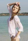 Girl in white shirt on coast lake Royalty Free Stock Image