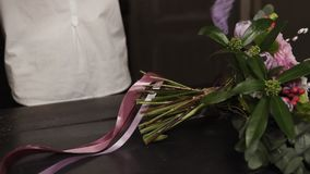 A girl in a white shirt cuts long pink ribbons and purple broad ribbons of guipure to decorate a bouquet of flowers on a. Table. Close up stock video footage