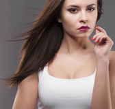 Girl in white shirt, gray background. Joyful young fashion brunette woman with pink lipstick hair motion Stock Images