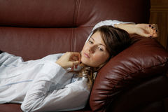 The girl in a white shirt lies on a sofa Stock Images