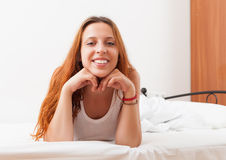 Girl in a white shirt lying on a soft bed sheets in the bed at h Royalty Free Stock Image