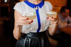 Girl holds in her hands two glasses with an alcoholic cocktail sour mix. Girl in a white shirt and with red manicure holds in her hands two glasses with an Royalty Free Stock Photo