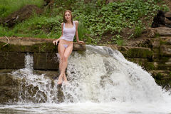 A girl in a white shirt standing in a waterfall. Royalty Free Stock Images