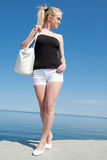 Girl in white shorts on background of the sea Royalty Free Stock Photo