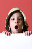 Girl with a white sigh. Young girl with a hat making surprised gesture and holding a white sigh Stock Photography