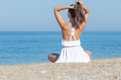 Girl in white sits on pebble seashore correcting hairstyle. Girl at the sea. Young woman in white sits on pebble seashore and correcting her hairstyle, rear view Stock Photography