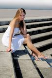 Girl in white sitting on steps Royalty Free Stock Photos