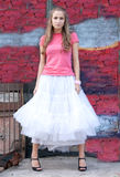 Girl in white skirt and pink T-shirt. In the city Royalty Free Stock Images