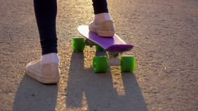 Girl in white sneakers riding skateboard pushing herself on asphalt road, slomo. stock video