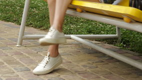 Girl in white sneakers is sitting on a swing stock video