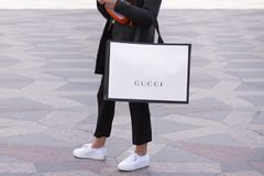 Girl with white sneakers standing holding a Gucci shopping bag on a street. Stock image royalty free stock photography