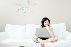 Girl on white sofa with laptop Royalty Free Stock Photo