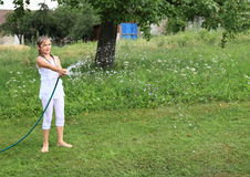 Girl in white splashing with garden hose Royalty Free Stock Photo