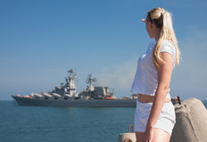 Girl in white sportwear at the sea. Young blond woman in white sportwear observes navy ship Stock Photo
