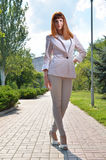 Girl in white standing on heels. Beautiful girl in white dress standing on the street Stock Image