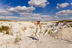 Girl in white suit and hat in full length, marble quarry, white marble Stock Photo