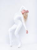 Girl in white suit posing. Young female contortionist in glossy vinyl suit Royalty Free Stock Photos
