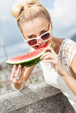 Girl in white summer dress eat watermelon Stock Image