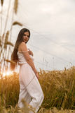 A girl in a white summer suit is standing in a field of wheat Royalty Free Stock Photo