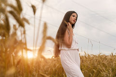 A girl in a white summer suit is standing in a field of wheat Stock Photo