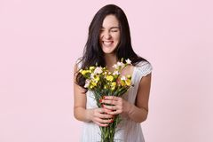 Girl in white sundress enjoys scent of flowers and sincerely laughs, enjoying great spring day on pink background, posing with. Closed eyes, being in high stock image