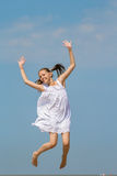 Girl in a white sundress jumps over the sea Stock Photos