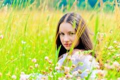 Girl in a white sundress lying on green grass Stock Images