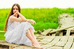 Girl in a white sundress resting on the bridge Stock Image