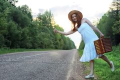 Girl in a white sundress and wicker suitcase walking on rails Royalty Free Stock Images