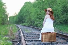 Girl in a white sundress and wicker suitcase walking on rails. Girl in a white sundress and a wicker suitcase walking on railsr Stock Image