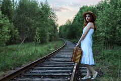 Girl in a white sundress and wicker suitcase walking on rails Stock Photography