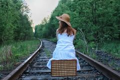 Girl in a white sundress and wicker suitcase walking on rails. Girl in a white sundress and a wicker suitcase walking on railsr Royalty Free Stock Photo
